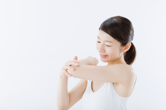 肘を見つめる女性