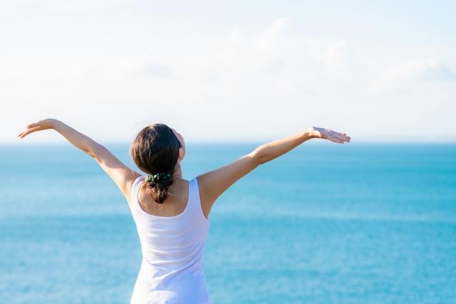 海で手を広げる女性